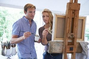 Man och kvinna framför en målarduk