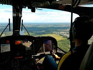 Man flyger helikopter över skogsområde
